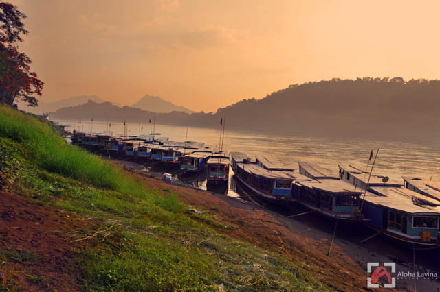 sunset over riverboats in Laos copyright Aloha Lavina.