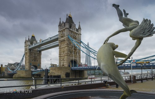 A daytime view of Tower Bridge, with David Wynnes's statue of Girl with Dolphin, in the foreground