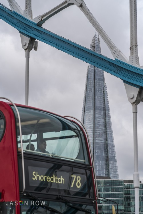 A red bus crosses Tower Bridge with the Shard London in the background