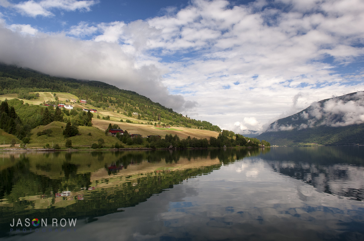 The near still water of dawn in the Fjords. By Jason Row Photography