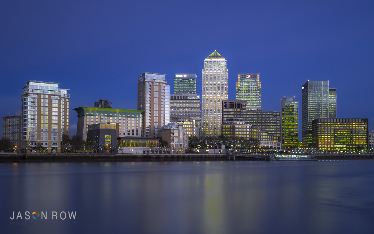 City lights reflected in moving water. By Jason Row Photography
