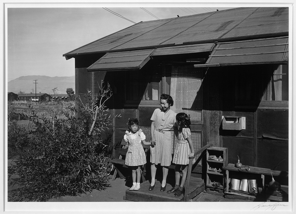 [Mrs. Yaeko Nakamura and her two children, Joyce Yuki (right) and Louise Tami (left), standing on the step at the entrance of a dwelling, Manzanar Relocation Center]