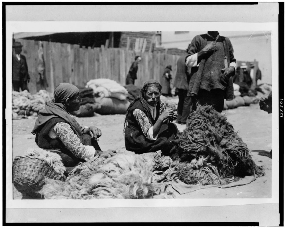 Bulgarian peasant women in market place, with piles of black and white wool