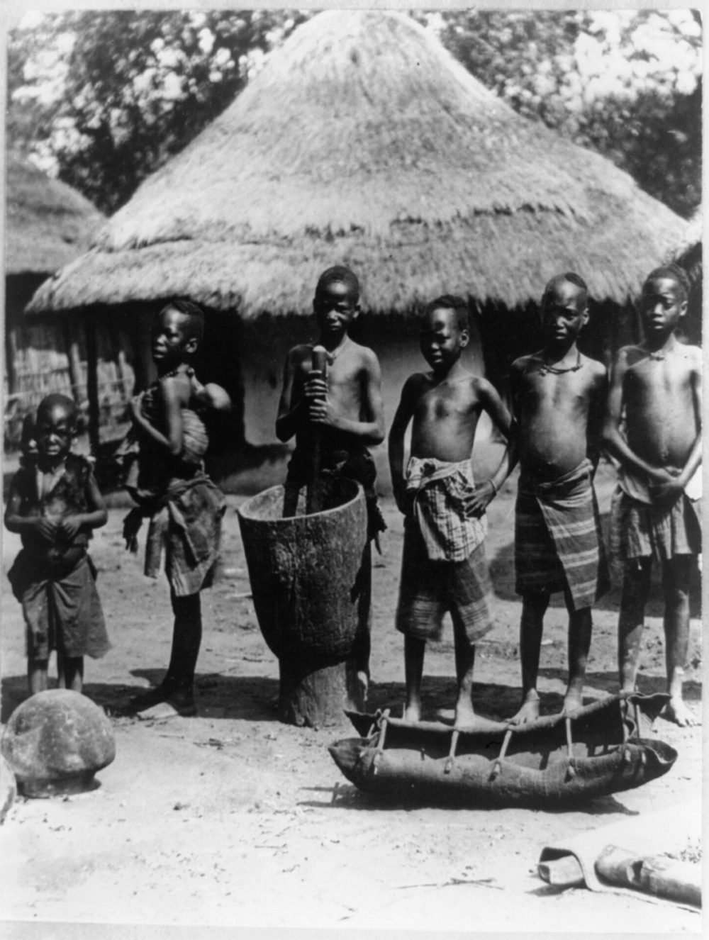 Seven native children posed in front of thatched-roof house, Portuguese East Africa