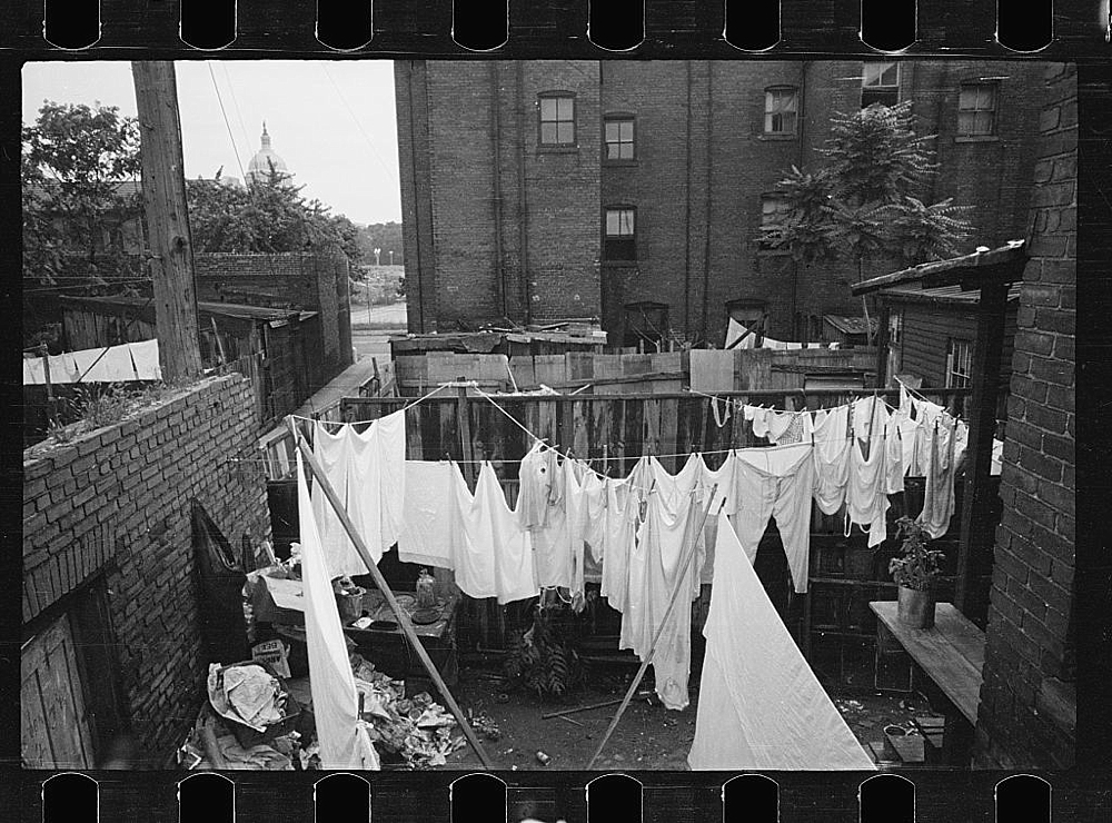 The Capitol can be seen in the background of this backyard slum scene