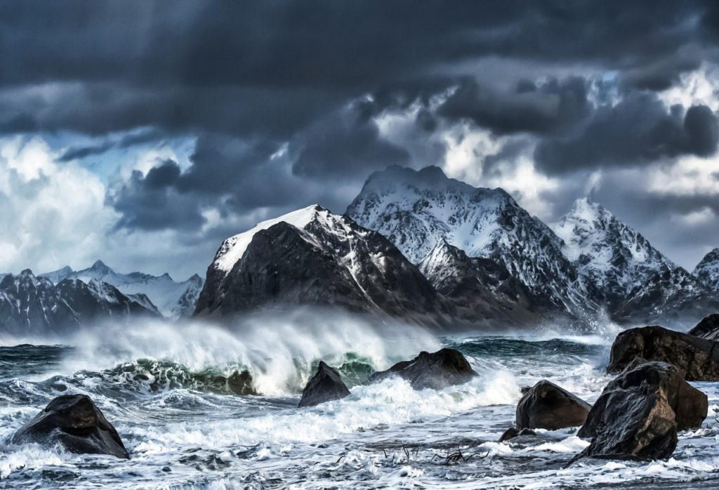 Storm over waves meeting mountains.
