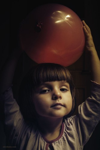 child holding red balloon