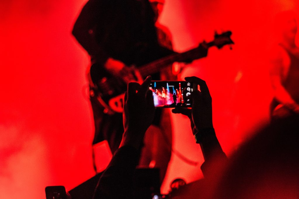 Person using camera phone taking photo of rock concert