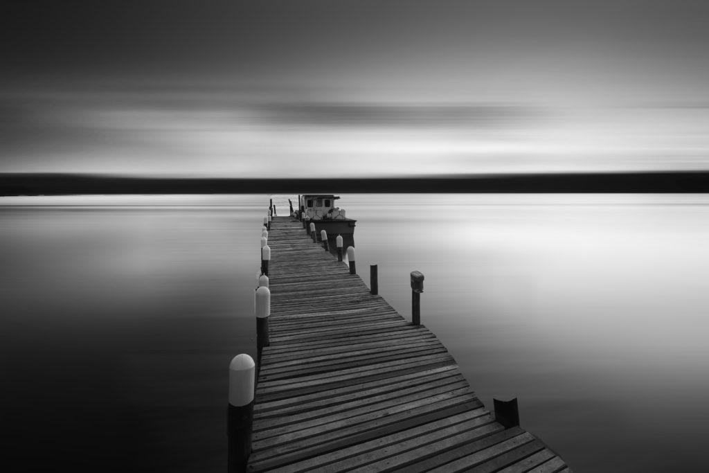 River with jetty and boat in black and white