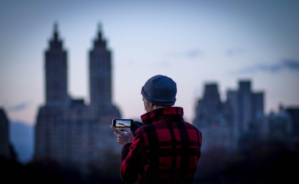 Man taking camera phone photograph of skyline