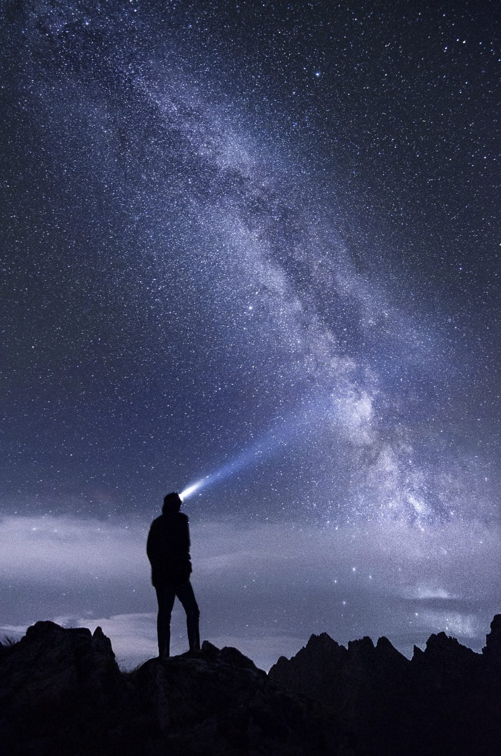 Man with torch in front of Milky Way