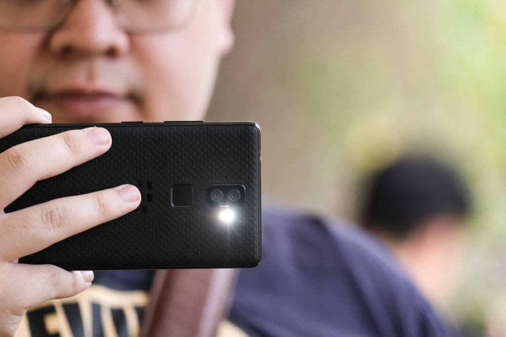 Man taking photo with phone with flash on