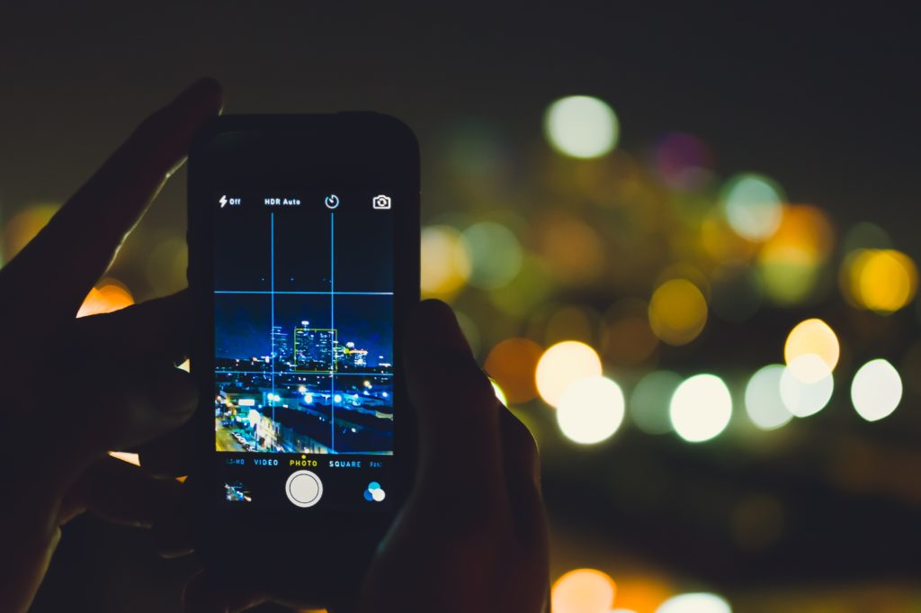 photo of phone taking image of city at night